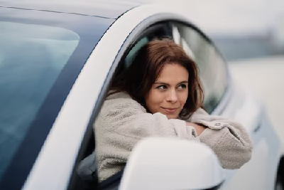 Lady in a car leaning on the window